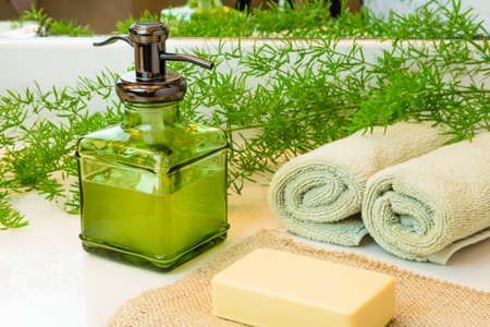 bar of soap: Pump green glass bottle with liquid castile soap. Beige bar soap on burlap. Rolled green towels in a spa setting. Green plant decor in background. Bathroom white countertop.