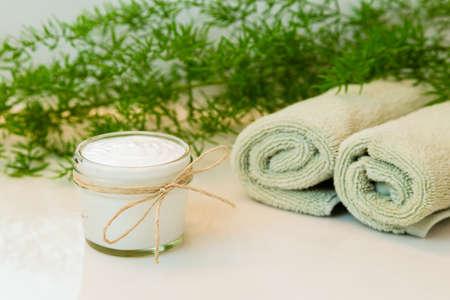 Glasmetselaar pot met witte crème, versierd met touw strikje. Gerold groen handdoeken in een spa-instelling. Groene plant decor op de achtergrond. Badkamer Wit aanrecht.