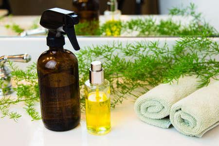 Bernstein und Klarglas Sprühflaschen. Rolled grüne Handtücher in einem Spa-Einstellung. Grüne Pflanze Dekor im Hintergrund. Badezimmer weiß Platte.
