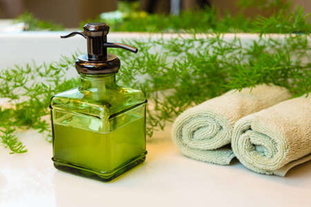 Pump green glass bottle with liquid castile soap. Rolled green towels in a spa setting. Green plant decor in background. Bathroom white countertop.