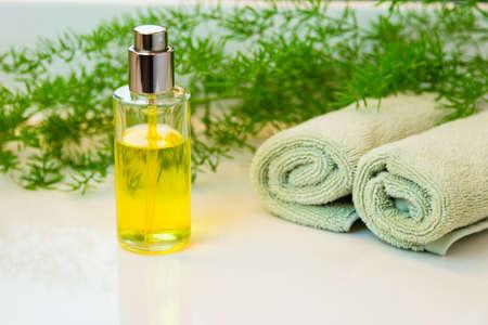 Klarglas-Sprühflasche mit gelber Flüssigkeit. Rolled grüne Handtücher in einem Spa-Einstellung. Grüne Pflanze Dekor im Hintergrund. Badezimmer weiß Platte.