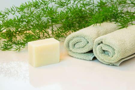 Savon naturel ou barre de shampooing. Laminés serviettes vertes dans un cadre de spa. Vert décor végétal en arrière-plan. Salle de bains comptoir blanc. Banque d'images - 59309165