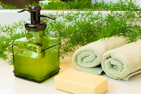 bar of soap: Pump green glass bottle with liquid castile soap. Beige bar soap. Rolled green towels in a spa setting. Green plant decor in background. Bathroom white countertop. Stock Photo