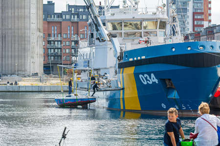 Malmo, Sweden - July 28, 2020: Swedish coast guard brings up to deck a sunken sailboat