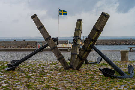 Three old anchors at Parapeten in Helsingborg, Sweden. This area has a long and close relationship with maritime activity. Swedish flag in the background