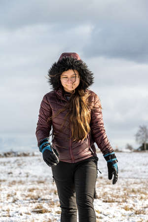 A teenage girl in a winter jacket with a hood in a cold winter landscape. Snow and a cloudy sky in the background
