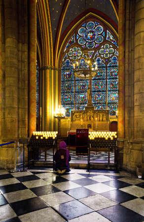 A girl praying in Notre dame de Paris