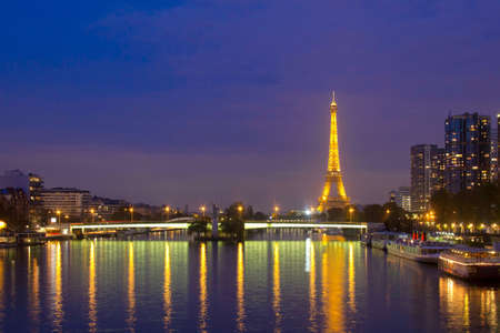 The eiffel tower at night with reflections in the Seine photo