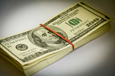 money packs: A stack of 100 dollar bills kept togheter by a rubber band