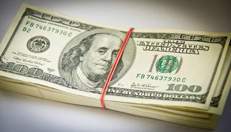 A stack of 100 dollar bills kept togheter by a rubber band Stock Photo - 25126792