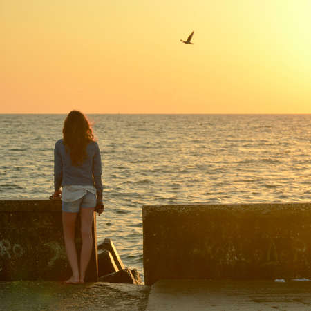 two and two thirds: A young woman watching the sea early in the morning Stock Photo