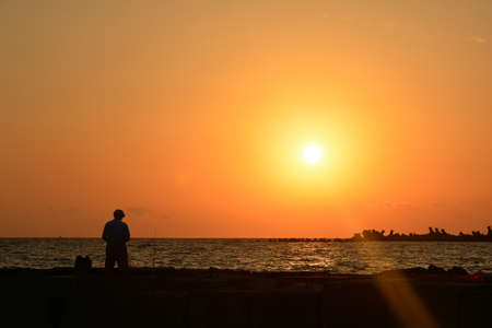 two and two thirds: An old man preparing to begin fishing during sunrise in Mamaia Stock Photo