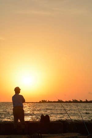 2 to 3 years: Un vecchio staglia contro il sole che sorge a Mamaia attesa che il pesce di cattura Archivio Fotografico