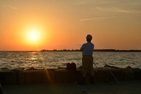 65 70 years: An old man silhouetted against the rising sun in Mamaia waiting for the fish to catch