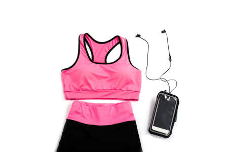 Top view fitness and sports clothes and accessories for females on white background: Sneakers, headphones, cell phone, dumbbells