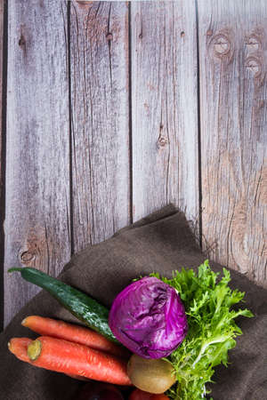 bowl of salad with vegetables and greens on wooden table Stock Photo