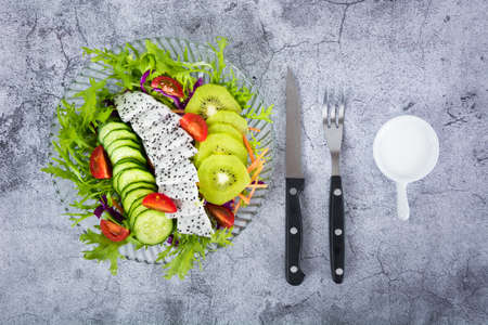 Mango lettuce salad with red peppers on a wooden plate