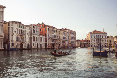 A gondolier rowing his Gondola on the famous Grand Canal, Venetian lagoon, Venice, Italy