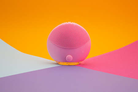 Back side of a mini magenta silicone vibrating facial cleansing brush on colorful background, close up with copy space