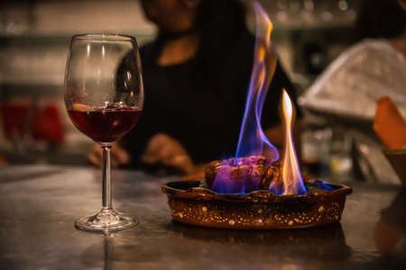 Traditional portuguese sausage chourico aka spanish chorizo sliced and flame-cooked over alcohol in an earthenware dish at the table served with a glass of chilled red port wine, a fado house, Lisbon, Portugal