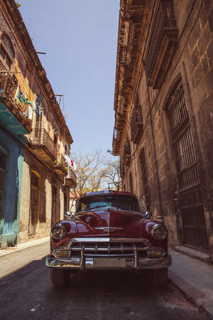 Close up shot of a classic (vintage) red shiny car parked in the streets of Havana, Cuba