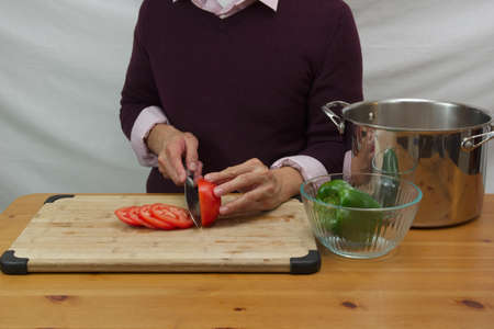 man cutting tomato