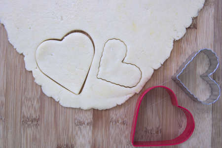 Heart-shaped cookie cutters with cookie dough Imagens