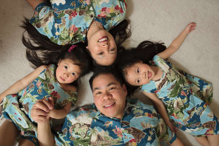 Asian family laying on floor smiling