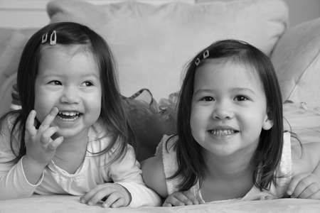 asian toddler: Smiling asian toddler sisters Stock Photo