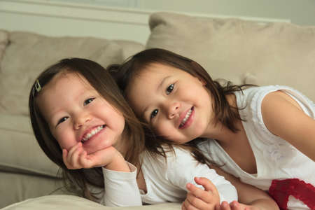giggling: Smiling asian toddler sisters Stock Photo