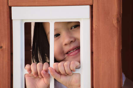 playhouse: Asian toddler smiling through playhouse window