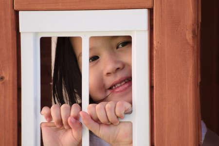 playhouse: Asian toddler smiling through playhouse window