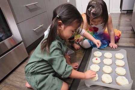 decorating: Asian toddlers decorating cupcakes