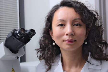 Asian female scientist sitting at microscope