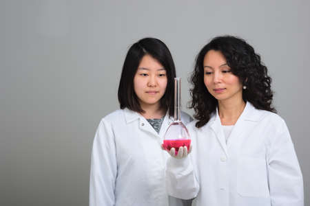 volumetric flask: Two asian female scientists examining volumetric flask Stock Photo
