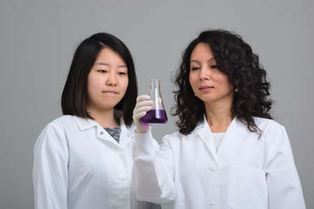 Two asian female scientists examining flask