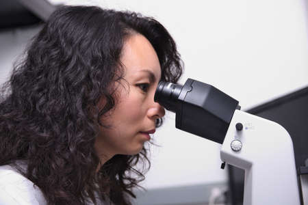 an eyepiece: Asian female scientist at microscope Stock Photo