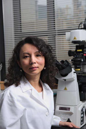 an eyepiece: Asian female scientist sitting at microscope