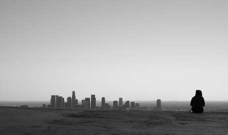 Single silhoutted seated figure next to skyline of downtown Los Angeles