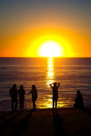 Family on the beach silhouetted by setting sun Stock fotó