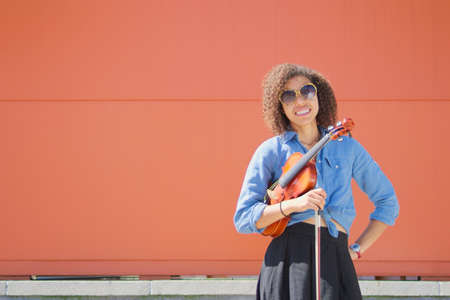 Smiling young female violinist holding violin and bow Reklamní fotografie