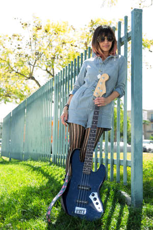 smirk: Woman posing with blue bass guitar outside
