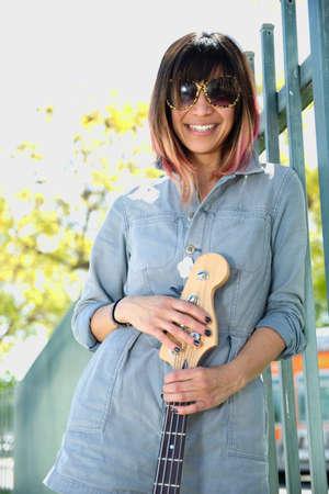 bass guitar women: Smiling female posing with guitar outdoors Stock Photo