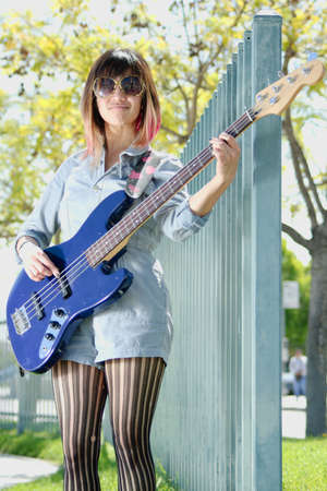 Young woman playing a blue bass guitar outside Stock Photo