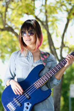 Female with sunglasses playing guitar outside