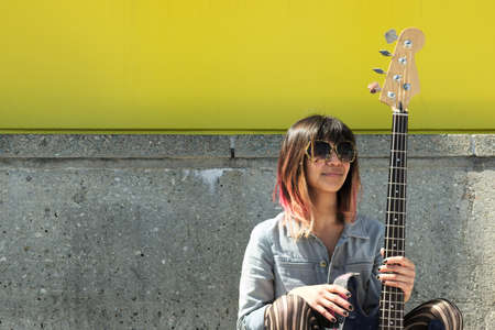 bass guitar women: Young lady sitting on ground and posing with guitar