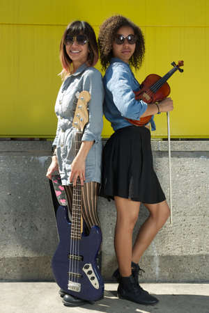 Two female musicians standing back to back holding instruments