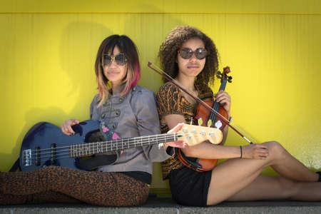 Vrouwen muzikanten zitten back to back bedrijf instrumenten Stockfoto