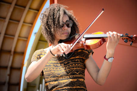 African American woman playing violin outdoors