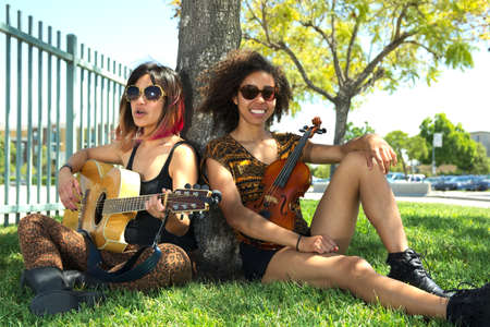 Two female musicians sitting by tree playing music